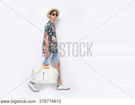 full length Summer man wearing sunglasses new stylish floral, plant ,leaves fern printed short shirts with hat , blue jeans shorts and white sneaker, shoes runway in studio