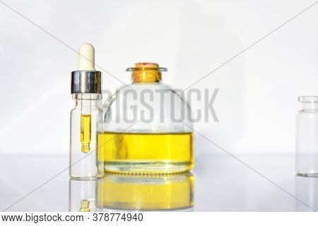 Glass Bottle With Cbd Oil, Thc Tincture And Hemp Leaves On A White Background Lab. Cosmetics Cbd Oil