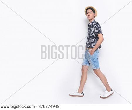 full length Summer man wearing new stylish floral, plant ,leaves fern printed short shirts with hat , blue jeans shorts and white sneaker, shoes runway in studio