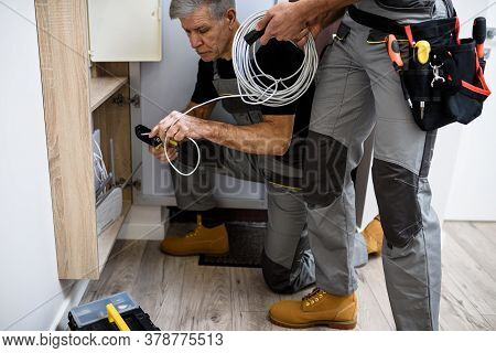 Cropped Shot Of Aged Electrician, Repairman In Uniform Working, Examining Cable, Checking Voltage In