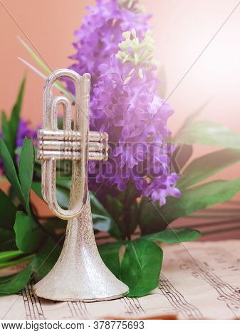 Trumpet On Musical Notes And Purple Flowers So Close