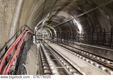 Subway Tunnel Rail Tracks. Red Tubes With Electric Cables.