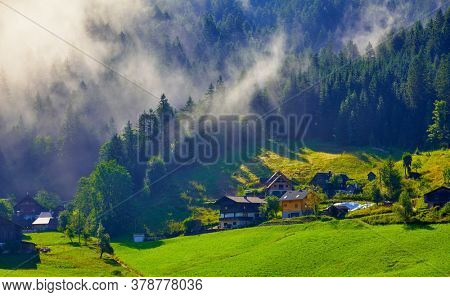 Austrian Alps Mountains. Alpine Village in forest and lawns with green grass. Foggy clouds on the trees. Traditional alpine village houses on the hills. Sunny morning.
