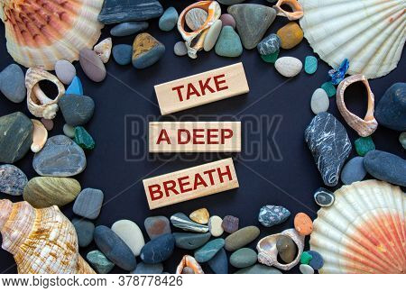 Text 'take A Deep Breath' On Wooden Blocks On A Beautiful Black Background. Sea Stones And Seashells