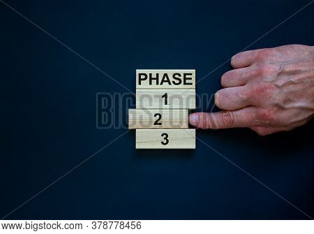 Wooden Blocks Form The Words 'phase, 1, 2, 3,' On Black Background. Male Hand. Beautiful Background.