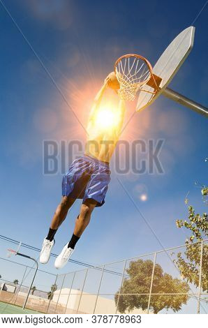 Man about to slam dunk ball on basketball court with strong sun shining lensflare