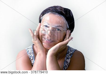 European Woman Makes A Pvc Film Cosmetic Mask.