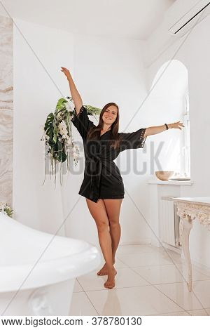 A Cute Young Woman Wearing A Black Robe Spend Time In The Bathroom. Happy Woman In The Morning In Th