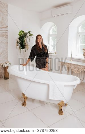 A Cute Young Woman Wearing A Black Robe Spend Time In The Bathroom.
