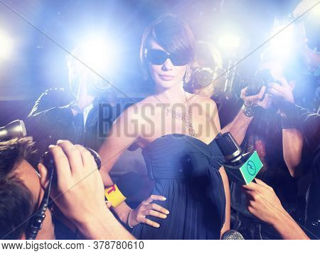 Glamourous Woman Surrounded by Paparazzi