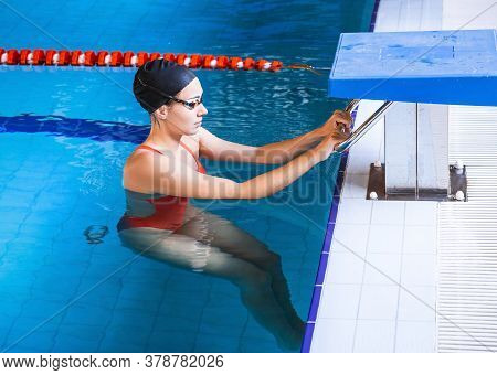 Young Woman Swimmer In A Swimsuit Getting Ready To Start Swimming In A Swimming Pool. Professional S
