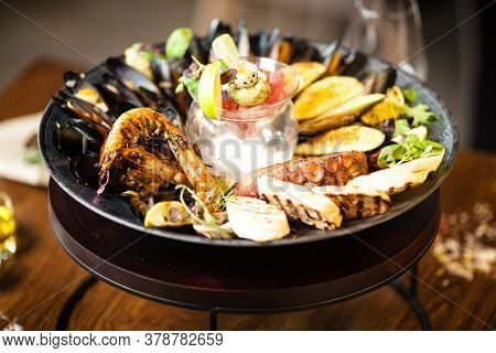 Seafood platter for 2-4 persons. Octopus, blue mussels, cooked green mussels, grilled tiger prawns, tuna tartare. Delicious seafood closeup served on a table for lunch in modern gourmet restaurant.