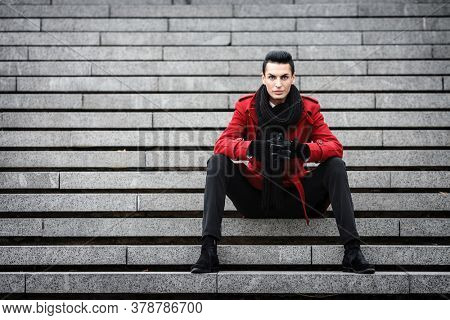 LGBTQ community lifestyle concept. Young homosexual man sits on a stairs. Handsome fashionable gay male model poses in cityscape outdoors. Wears red coat, gloves, and black scarf.