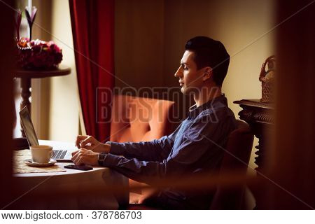 LGBTQ community lifestyle concept. Young homosexual man sits at the table in old-fashioned city cafe. Handsome gay male businessman works on laptop computer while having a break at lunch.