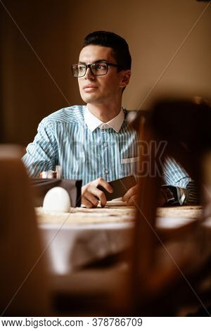 LGBTQ community lifestyle concept. Young homosexual man sits at the table in old-fashioned city cafe. Handsome smiling gay male businessman poses while having a break at lunch.
