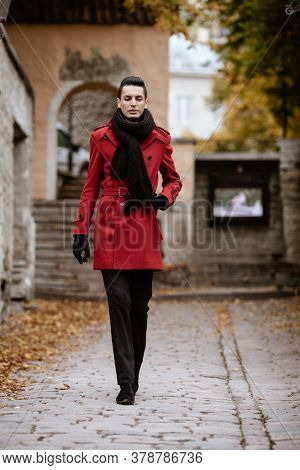 LGBTQ community lifestyle concept. Young homosexual man walks down a street. Handsome fashionable gay male model poses in cityscape outdoors. Wears red coat, gloves, and black scarf.