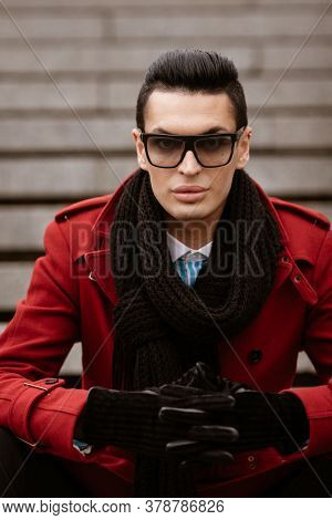 LGBTQ community lifestyle concept. Young homosexual man sits on a stairs. Handsome fashionable gay male model poses in cityscape outdoors. Wears red coat, gloves, sunglasses and black scarf.