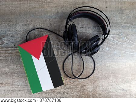 Headphones And Book. The Book Has A Cover In The Form Of Palestine Flag. Concept Audiobooks. Learnin