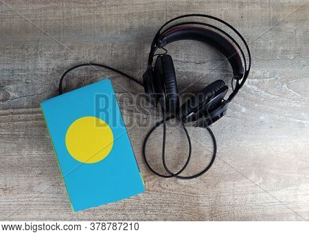 Headphones And Book. The Book Has A Cover In The Form Of Palau Flag. Concept Audiobooks. Learning La