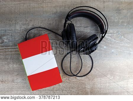 Headphones And Book. The Book Has A Cover In The Form Of Peru Flag. Concept Audiobooks. Learning Lan