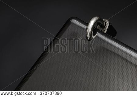 Locked Steel Padlock In A Drilled Hole Of The Black Laptop On Dark Background. Concept Of Protecting