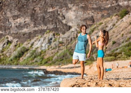 Fitness couple doing stretching exercises before going on a beach run. Active fit runner couple running together doing cardio workout outdoor leg and arm stretch.
