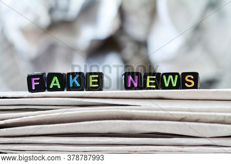 The Inscription Fake News On The Stack Of Newspapers On The Background Of A Crumpled Newspaper. Conc