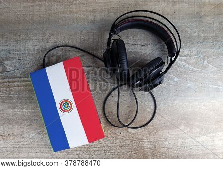 Headphones And Book. The Book Has A Cover In The Form Of Paraguay Flag. Concept Audiobooks. Learning