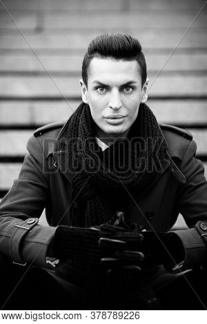 LGBTQ community lifestyle concept. Young homosexual man sits on a stairs. Handsome fashionable gay male model poses outdoors. Wears red coat, gloves, and black scarf. Black and white monochrome