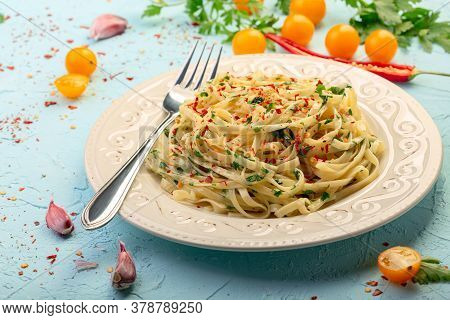 Linguini Pasta With Hot Chili Is Served With Garlic And Parsley Sauce On A Ceramic Plate. Italian Cu