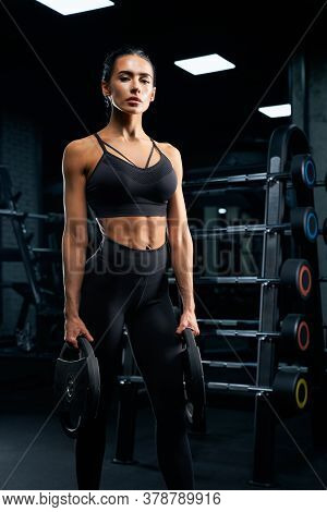 Portrait Of Fitnesswoman With Braids Posing Near Stand With Sports Equipment And Holding Weights. Sr