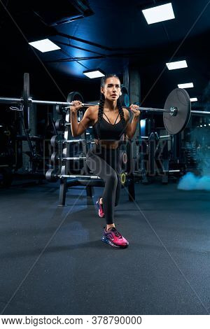Side View Of Brunette Female Bodybuilder With Long Braids Doing Lunges Using Barbell. Srtong Woman W