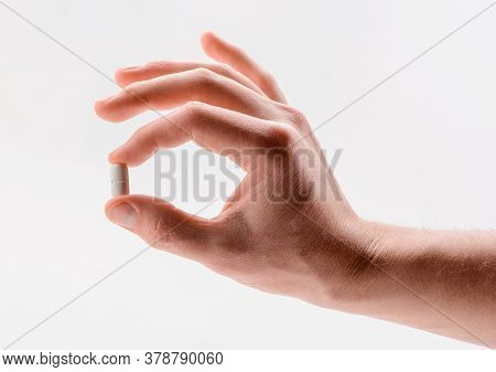 Hand Holding A White Caplet Pill Between Fingers