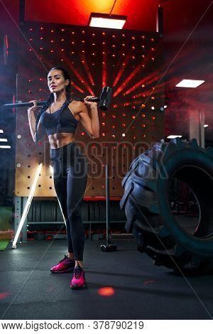 Side View Of Muscular Woman In Sportswear Holding Sledgehammer On Shoulders Near Tire Wheel. Full Le
