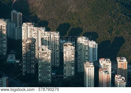 Aerial View Of Apartment Buildings With Sunlight On Top Of Them And A Hill Behind