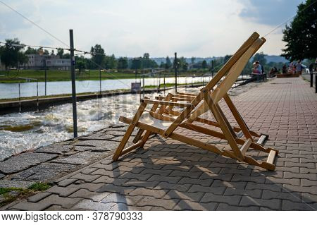 Deck Chairs At The Side Of A White Water River.