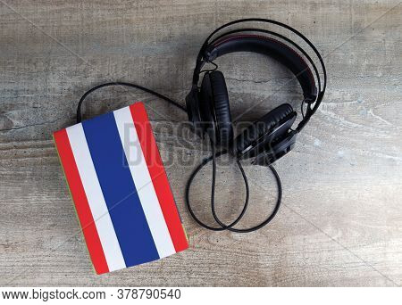 Headphones And Book. The Book Has A Cover In The Form Of Thailand Flag. Concept Audiobooks. Learning