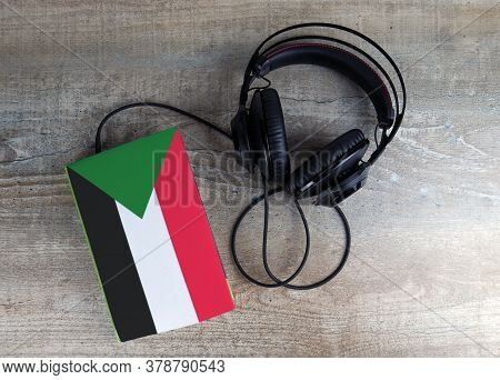 Headphones And Book. The Book Has A Cover In The Form Of Sudan Flag. Concept Audiobooks. Learning La