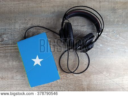 Headphones And Book. The Book Has A Cover In The Form Of Somalia Flag. Concept Audiobooks. Learning