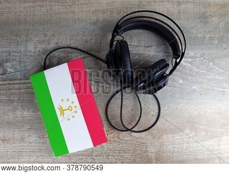 Headphones And Book. The Book Has A Cover In The Form Of Tajikistan Flag. Concept Audiobooks. Learni