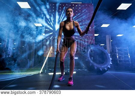 Stunning Muscular Woman In Black Sports Underwear Training In Gym With Ropes In Dark Atmosphere And