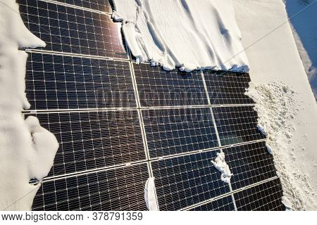 Close Up Surface Of A House Roof Covered With Solar Panels In Winter With Snow On Top. Energy Effici