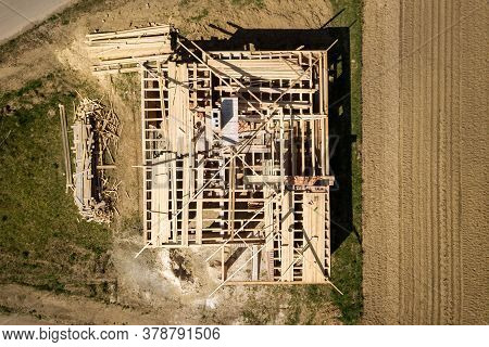 Aerial View Of Unfinished Brick House With Wooden Roof Frame Structure Under Construction.