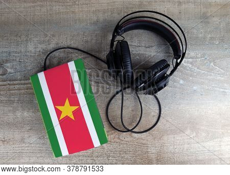 Headphones And Book. The Book Has A Cover In The Form Of Suriname Flag. Concept Audiobooks. Learning