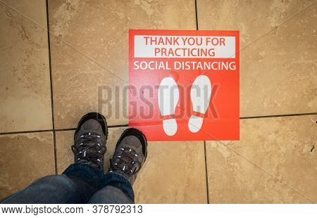 A Pair Of Hiking Boots Near A Red Thank You For Practicing Social Distancing Sign At A Supermarket