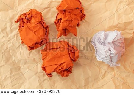 Three Red Crumpled Paper And One White Paper Lie On An Orange Slightly Crumpled Sheet Of Paper