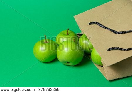 Green Apples On A Green Background. Apples Fell Out Of A Paper Bag.