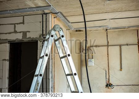 Aluminium Ladder And Electrical Cables Laid In Protective Corrugation Installed On The Ceiling And W
