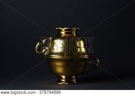 Gold Tea Cups On A Black Background. One Teacup Rests On Top Of The Other.