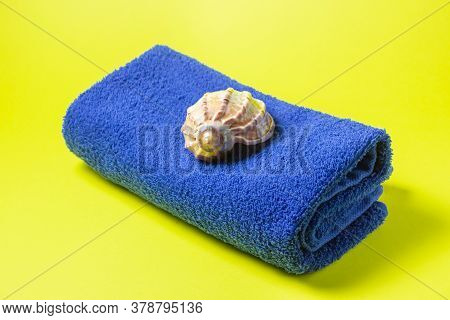 Blue Towel On A Yellow Background. The Seashell Lies On A Towel. A Long Awaited Vacation. A Trip To